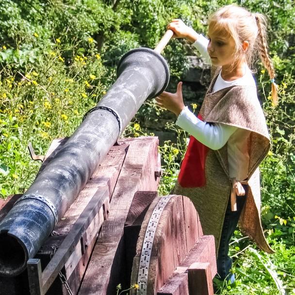 Jeune fille déguisée armant un canon médiéval lors d'une animation
