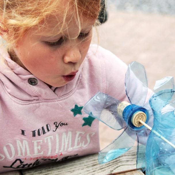 Petite fille soufflant sur un bricolage en éolienne